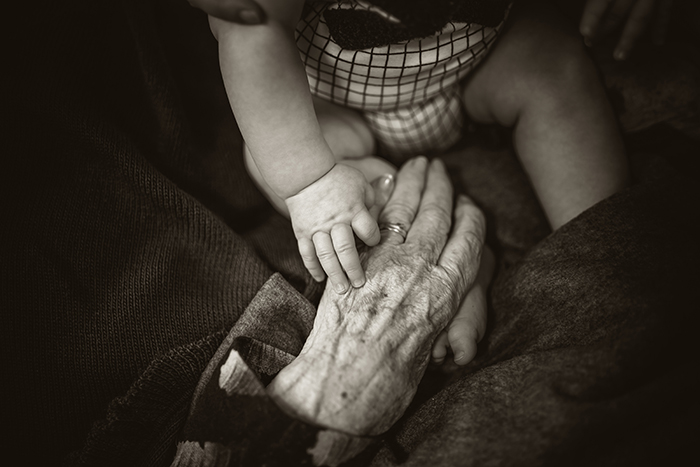 photography trends old person putting hand on babys hand - 20 tendenze fotografiche top di cui essere a conoscenza nel 2020