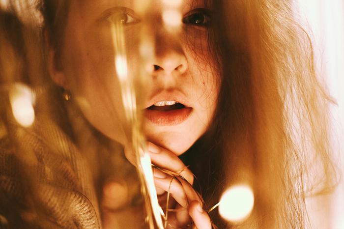 tungsten light girl peeking through decorations - 8 suggerimenti per scattare foto con luce al tungsteno blog