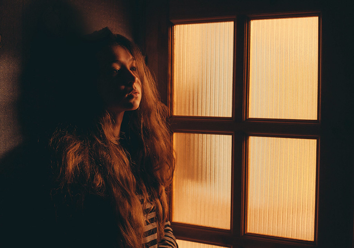 tungsten light girl posing next to glass door - 8 suggerimenti per scattare foto con luce al tungsteno blog